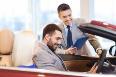 Pares felices con el concesionario de coches en salón del automóvil o salón Fotos de archivo libres de regalías