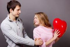 Pares felices con el globo rojo. Día de tarjetas del día de San Valentín Imagen de archivo