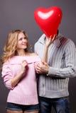 Pares felices con el globo rojo. Día de tarjetas del día de San Valentín Fotografía de archivo