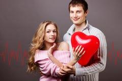 Pares felices con el globo rojo. Día de tarjetas del día de San Valentín Imágenes de archivo libres de regalías