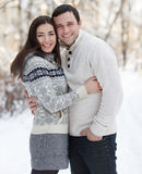 Pares felices con el muérdago que se divierte en el parque del invierno Foto de archivo libre de regalías