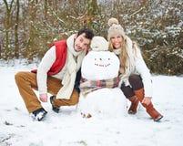 Pares felices con el muñeco de nieve en invierno Fotos de archivo