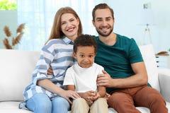 Pares felices con el muchacho afroamericano adoptado Imagen de archivo libre de regalías