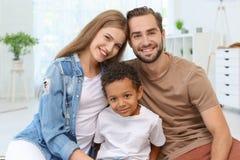 Pares felices con el muchacho afroamericano adoptado Imágenes de archivo libres de regalías