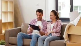 Pares felices con el ordenador de la PC de la tableta en el nuevo hogar metrajes