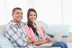 Pares felices con el ordenador portátil que se sienta en el sofá Imágenes de archivo libres de regalías