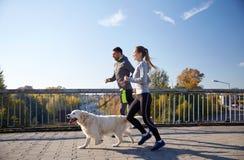 Pares felices con el perro que corre al aire libre Imagenes de archivo