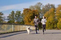 Pares felices con el perro que corre al aire libre Fotos de archivo