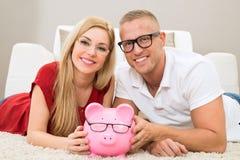 Pares felices con el piggybank Foto de archivo