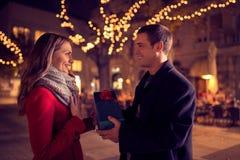 Pares felices con el regalo de la Navidad y del Año Nuevo en la calle Foto de archivo