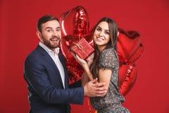 Pares felices con el regalo y los globos en un fondo rojo foto de archivo libre de regalías