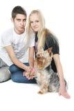 Pares felices con el terrier de yorkshire sobre blanco Fotos de archivo