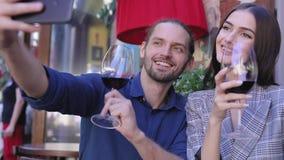 Pares felices con el vino que toma las fotos en el teléfono en el restaurante metrajes