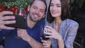 Pares felices con el vino que toma las fotos en el teléfono en el restaurante almacen de video