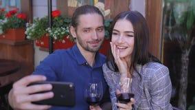 Pares felices con el vino que toma las fotos en el teléfono en el restaurante almacen de metraje de vídeo