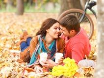Pares felices con la bicicleta en parque del otoño Fotografía de archivo libre de regalías