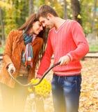 Pares felices con la bicicleta en parque del otoño Imagen de archivo libre de regalías