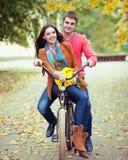Pares felices con la bicicleta en parque del otoño Foto de archivo