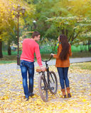 Pares felices con la bicicleta en parque del otoño Fotografía de archivo