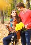 Pares felices con la bicicleta en parque del otoño Fotos de archivo