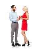 Pares felices con la caja de regalo en forma de corazón roja Foto de archivo libre de regalías