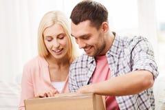 Pares felices con la caja del paquete en casa Fotografía de archivo