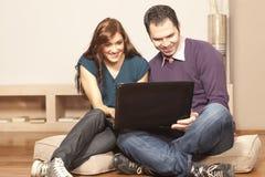 Pares felices con la computadora portátil en el suelo Fotos de archivo libres de regalías