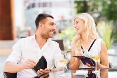 Pares felices con la cuenta que paga de la cartera en el restaurante Foto de archivo