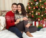 Pares felices con la Navidad y el regalo del Año Nuevo en casa Árbol de abeto con la decoración Concepto de las vacaciones de inv Imagen de archivo