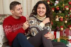 Pares felices con la Navidad y el regalo del Año Nuevo en casa Árbol de abeto con la decoración Concepto de las vacaciones de inv Fotografía de archivo libre de regalías