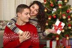Pares felices con la Navidad y el regalo del Año Nuevo en casa Árbol de abeto con la decoración Concepto de las vacaciones de inv Imagenes de archivo