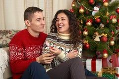 Pares felices con la Navidad y el regalo del Año Nuevo en casa Árbol de abeto con la decoración Concepto de las vacaciones de inv Fotos de archivo libres de regalías