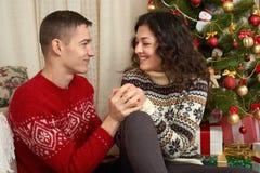 Pares felices con la Navidad y el regalo del Año Nuevo en casa Árbol de abeto con la decoración Concepto de las vacaciones de inv Foto de archivo libre de regalías