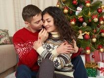 Pares felices con la Navidad y el regalo del Año Nuevo en casa Árbol de abeto con la decoración Concepto de las vacaciones de inv Fotografía de archivo