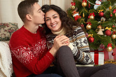 Pares felices con la Navidad y el regalo del Año Nuevo en casa Árbol de abeto con la decoración Concepto de las vacaciones de inv Foto de archivo