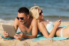 Pares felices con la PC de la tableta que toma el sol en la playa Fotografía de archivo libre de regalías
