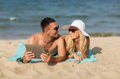Pares felices con la PC de la tableta que toma el sol en la playa Foto de archivo libre de regalías