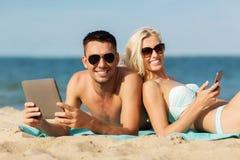 Pares felices con la PC de la tableta que toma el sol en la playa Fotografía de archivo