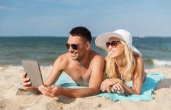 Pares felices con la PC de la tableta que toma el sol en la playa Imagenes de archivo