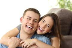 Pares felices con la sonrisa blanca en casa imágenes de archivo libres de regalías