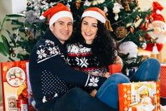 Pares felices con la sonrisa de los sombreros de Papá Noel foto de archivo libre de regalías