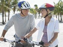 Pares felices con las bicicletas en la playa tropical Imágenes de archivo libres de regalías
