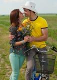 Pares felices con las flores y la bicicleta al aire libre Imagen de archivo libre de regalías