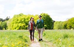 Pares felices con las mochilas que caminan al aire libre Fotografía de archivo libre de regalías