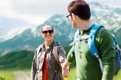 Pares felices con las mochilas que viajan en montañas Fotos de archivo libres de regalías