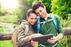 Pares felices con las mochilas y PC de la tableta al aire libre Fotografía de archivo