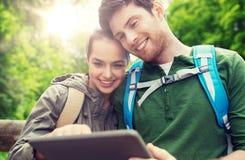 Pares felices con las mochilas y PC de la tableta al aire libre Imágenes de archivo libres de regalías