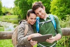 Pares felices con las mochilas y PC de la tableta al aire libre Fotografía de archivo libre de regalías