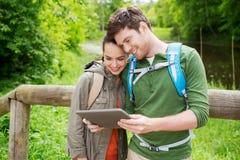 Pares felices con las mochilas y PC de la tableta al aire libre Foto de archivo libre de regalías