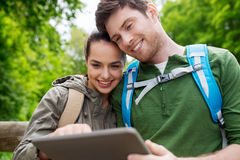 Pares felices con las mochilas y PC de la tableta al aire libre Imagen de archivo